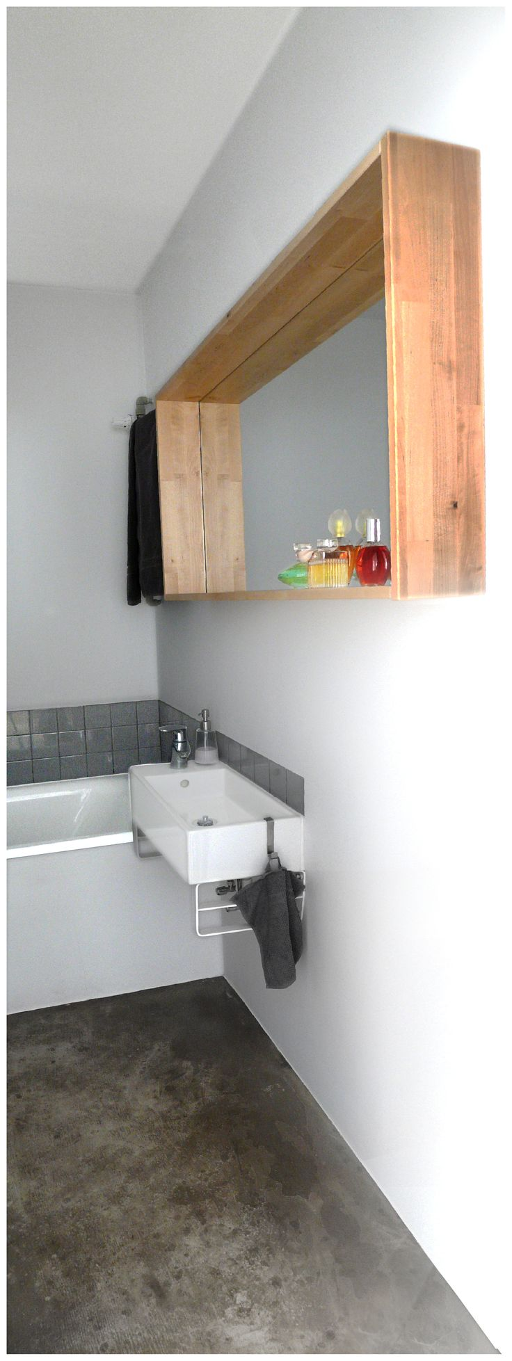 www.kwadratowymetr.pl Concrete floor in simple white and grey bathroom.