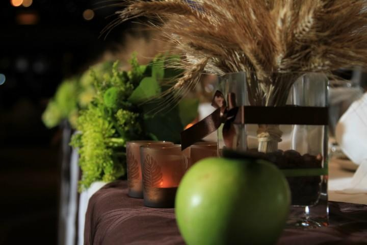 Green apples with brown paper leaves for seating arrangement. Wheat and coffee beans for table center pieces. Brown napkins for center of table. Brown harvest candle holders.