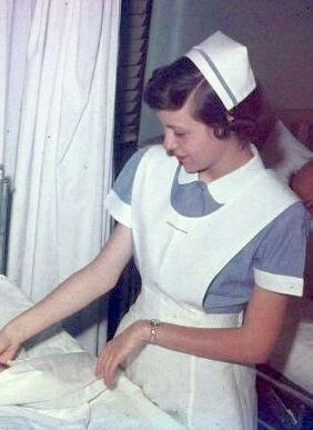 Student Nurse in full uniform, note blue stripe on cap - usually an indication of education level at that point - Freshman, Junior, Senior.