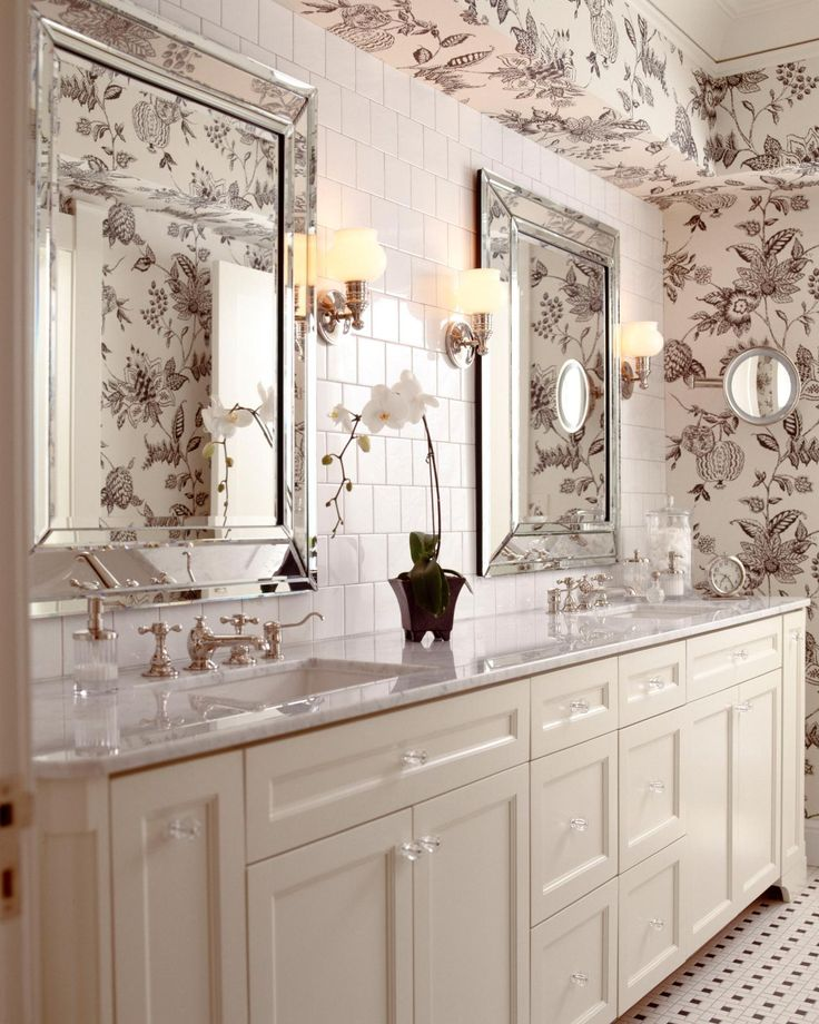 A creamy vanity, marble countertop and white tile backsplash give this bathroom a bright, breezy atmosphere. Patterned wallpaper creates movement and lends sophistication to the space. Beveled mirrors add a touch of glam.
