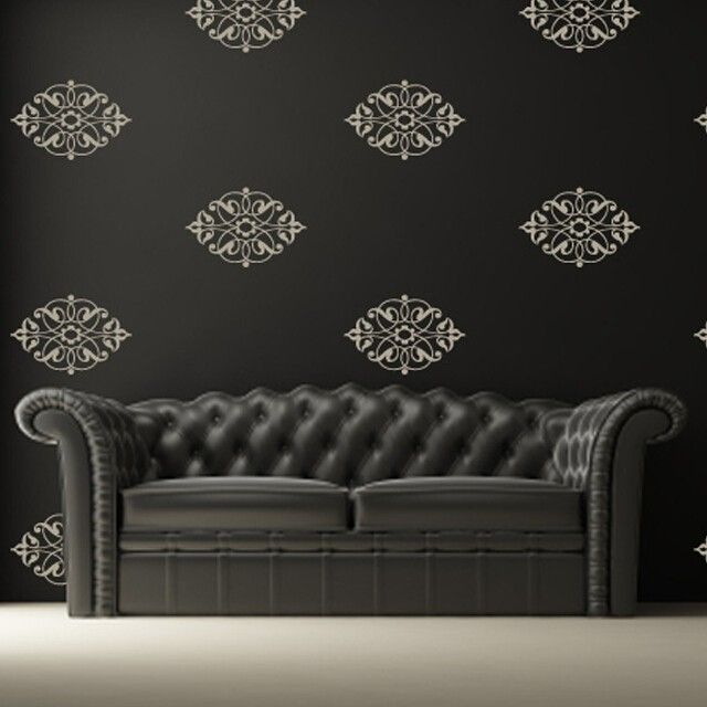 White damask wall decals placed evenly as a pattern on a black wall above a black victorian style couch.