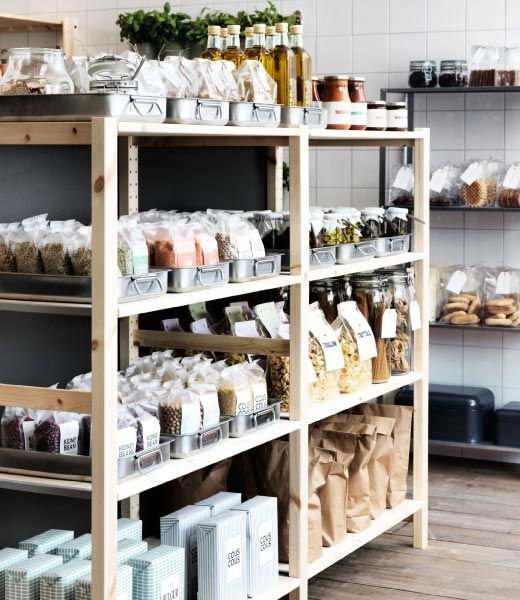 Wood shelves with stainless steel roasting tins filled with bags of couscous and spices