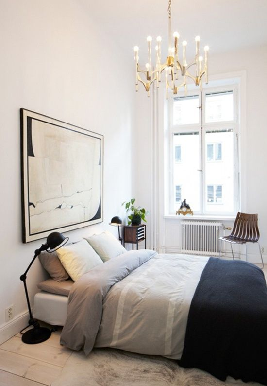 small space bedroom with large chandelier and simple minimal styling