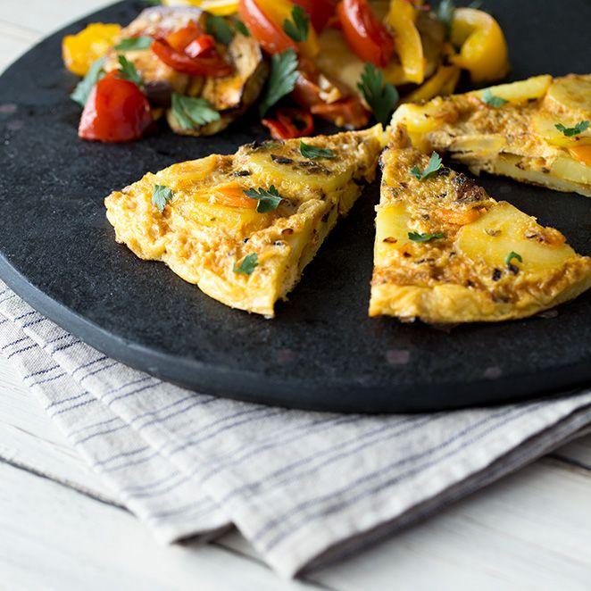 Die spanische Version des Omeletts wird mit deftigen Kartoffeln und würzigem Käse zubereitet und ist mit saftig-aromatischem Ofengemüse serviert einfach unwiderstehlich.