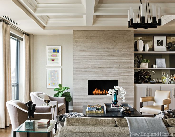 The entry sports a rosewood-topped buffet by Holly Hunt, sleek sconces by Jonathan Browning and a colorful painting by Tristan Govignon. New England Home