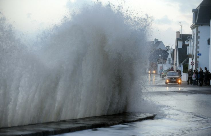People gather on the sidewalk as waves batter the sea wall in Ile-Tudy, in the Finistere department of Brittany, northwestern France, on Jan. 3, 2014.