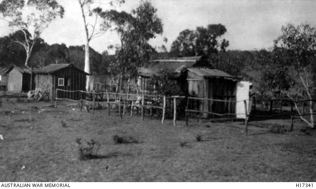 BERRIMA, NSW, C. 1918. HUTS BUILT FROM BUSH MATERIALS BY INTERNEES FROM THE GERMAN CONCENTRATION (INTERNMENT) CAMP. THESE HUTS ARE PROBABLY BESIDE THE BERRIMA RIVER IN THE SECTION USED FOR RECREATIONAL ACTIVITIES BY THE INTERNEES DURING THEIR PAROLE HOURS.