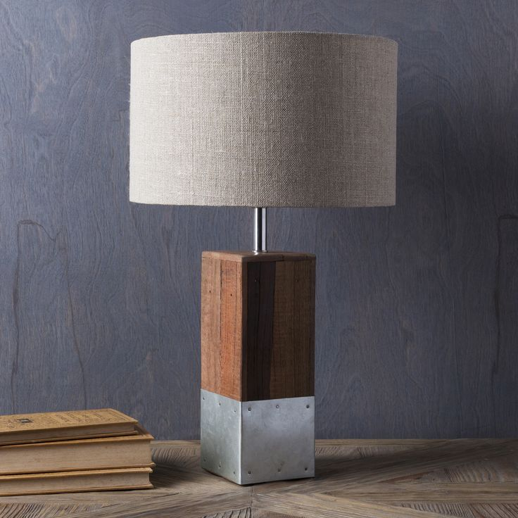Sleek and rustic, our Restoration Wood & Metal Table Lamp Brown with Oatmeal Shade features recycled wood, iron and stainless steel topped with a beautiful green cotton cylinder shade. This industrial, textural and rugged lamp will translate into any space beautifully.