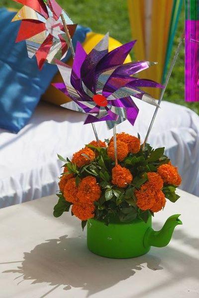 teapot table cnterpiece , quirky table centerpieces , pinwheels , floral arrangements , genda flowers , fun, kitsch mehendi decor , funky mehendi decor ideas