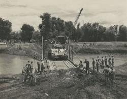 Shermanntank van de Mariniersbrigade rijdt over noodbrug te Goenoengsari