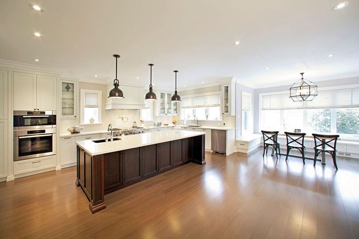 Massive island with a quartz countertop, glass backsplash, stainless steel industrial appliances and a dining area make for a bright kitchen built far better than good enough.