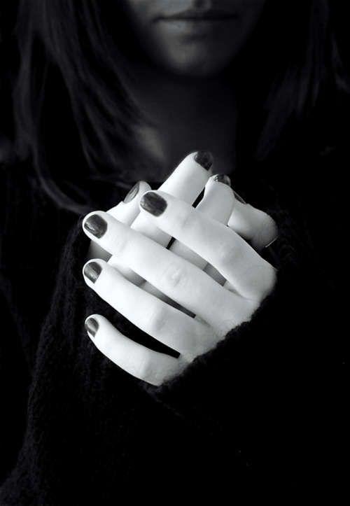 Pale hands, black nails.