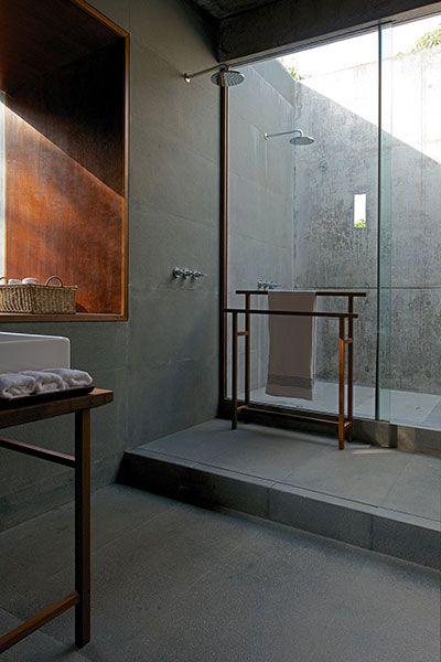 master bathroom with outdoor shower courtyard, black granite, frameless glass door, timber window frame, towel rack, skylight, stone shower drain