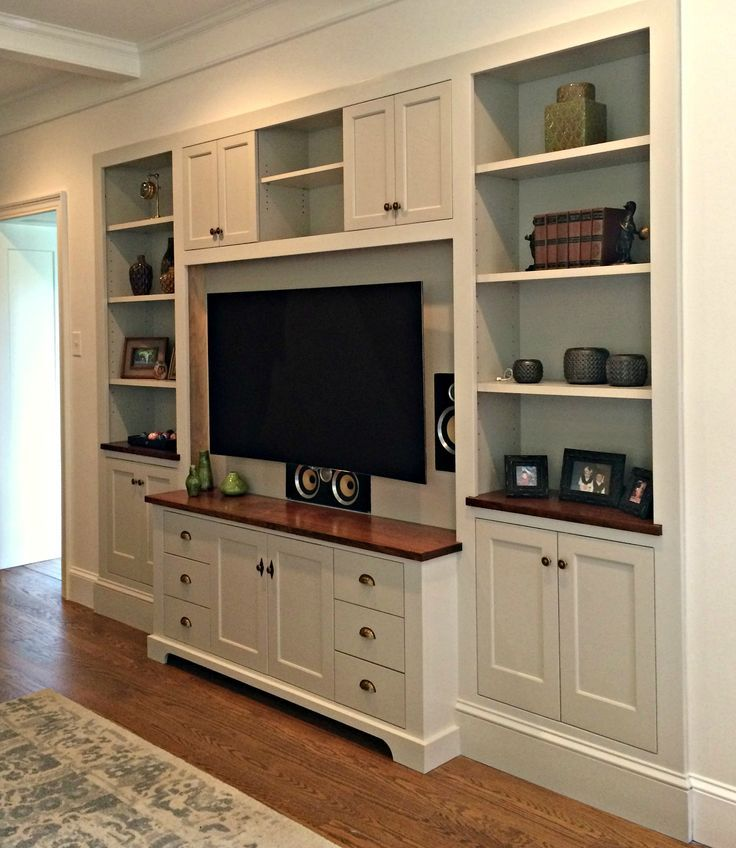 This custom entertainment center was recessed into the wall creating a seamless look. Painted in Benjamin Moore's Revere Pewter with cherry wood top and antique brass hardware.