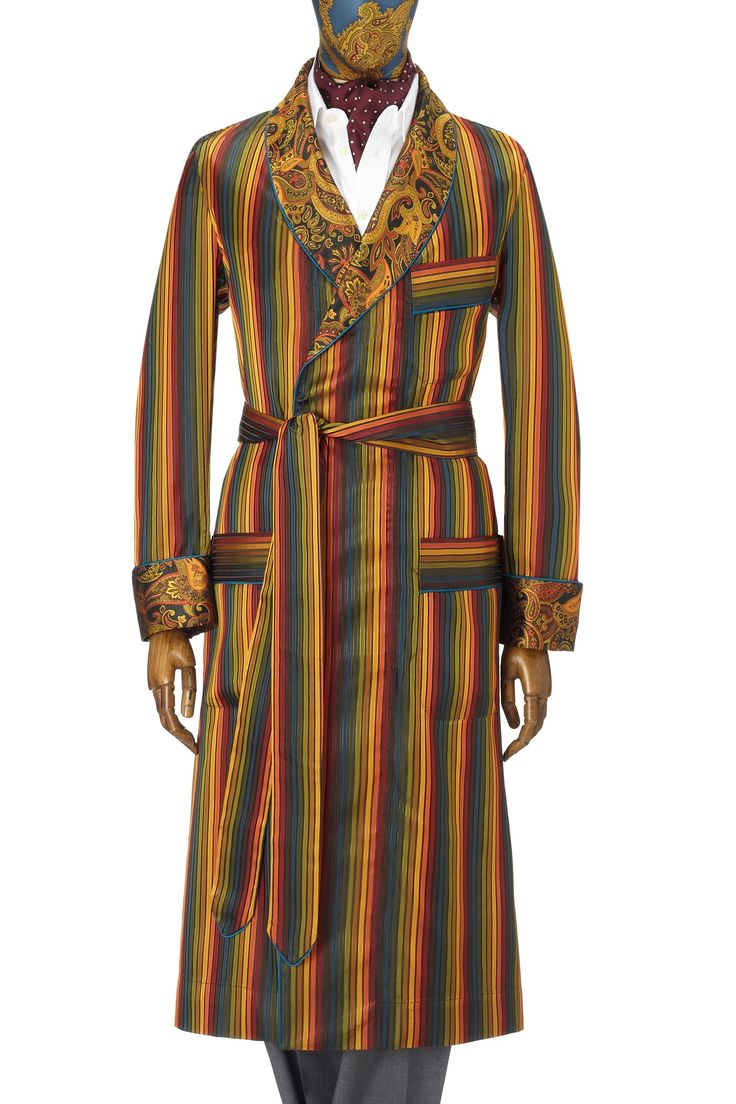 Multi Stripe Silk Gown  This gown is an opulent mix of multi coloured satin stripes and rich paisley.  The rich hues of green, gold, orange, petrol and deep red in the stripes, sit perfectly with the warm gold and burnt orange tones of the paisley shawl collar.  The gown is piped throughout in petrol satin and features deep gauntlet cuffs, patch pockets and an outbreast welt.  Made in England