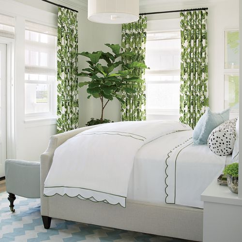 Vibrant green draperies in a fig leaf pattern frame the windows in our Coronado Showhouse master bedroom, designed by Betsy Burnham and Max Humphrey. The shade is echoed in the sweet bedding accent stitch.