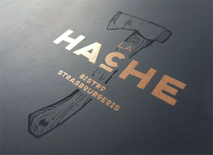 La Hache —french for axe— displays its clean black and white menu with axe and other grinding object silhouette icons across its pages. The varnish on the cover gives it an elegant touch that flows throughout the rest of the pages.