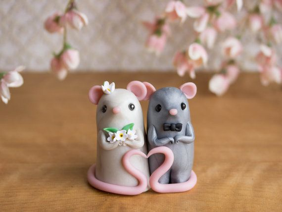 This keepsake, handmade wedding cake topper features a pair of cute mice who have big pink ears, paws that curls into delicate spirals and long
