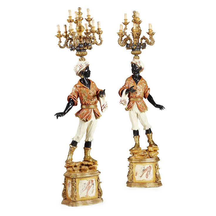 PAIR OF ITALIAN PAINTED AND PARCEL GILT CARVED WOOD BLACKAMOOR TORCHERES the standing figures supporting fruit filled urns issuing giltwood nine scrolling candle arms, on a shaped moulded plinth base with acanthus scroll corners, fitted for electricity