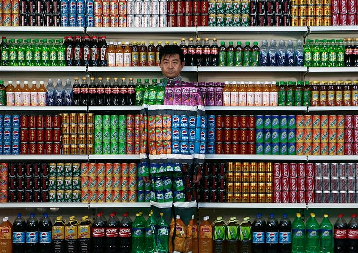 "Chinese artist Liu Bolin waits for his colleagues to put a finishing touch on him to blend into rows of soft drinks in his artwork entitled ""Plasticizer"" to express his speechlessness at use of plasticizer in food additives, in his studio at the 798 Art District in Beijing, China, on August 10, 2011. (AP Photo)"