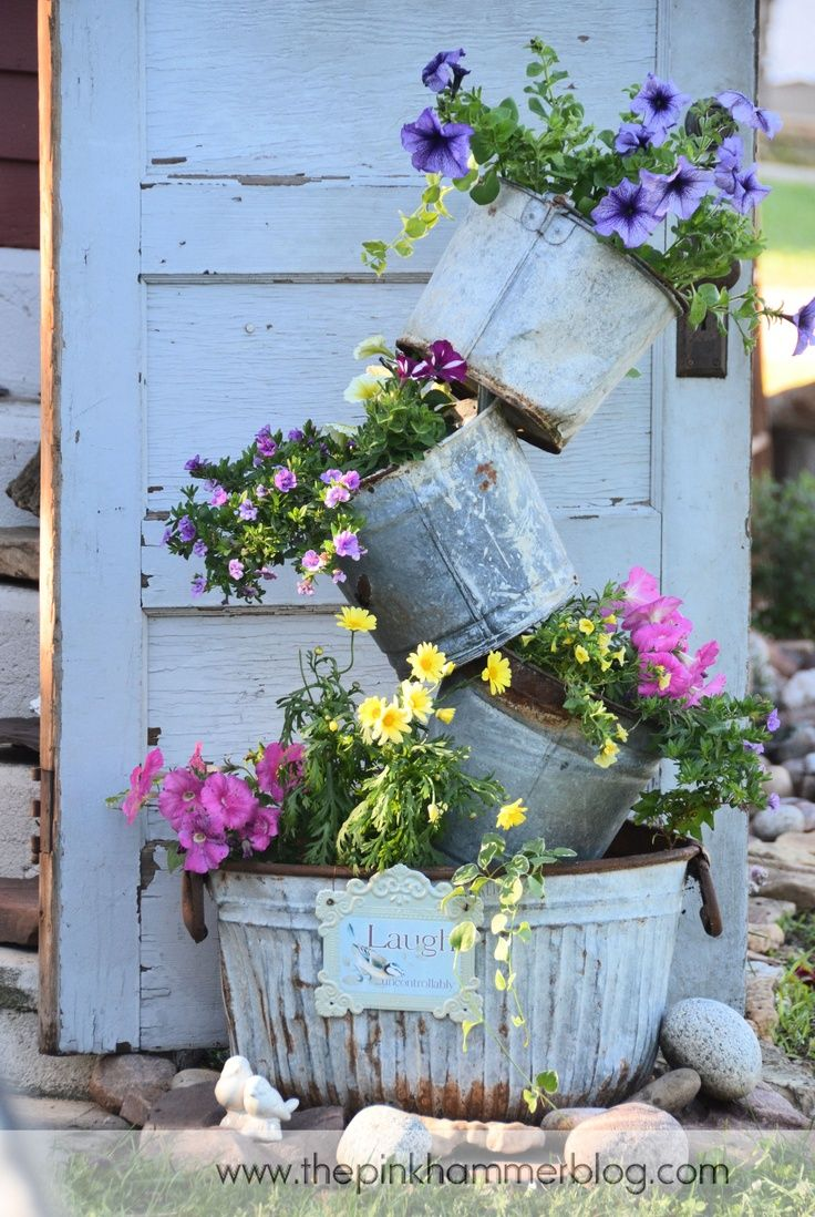 Flowers displayed in galvanized containers in front of old vintage door.