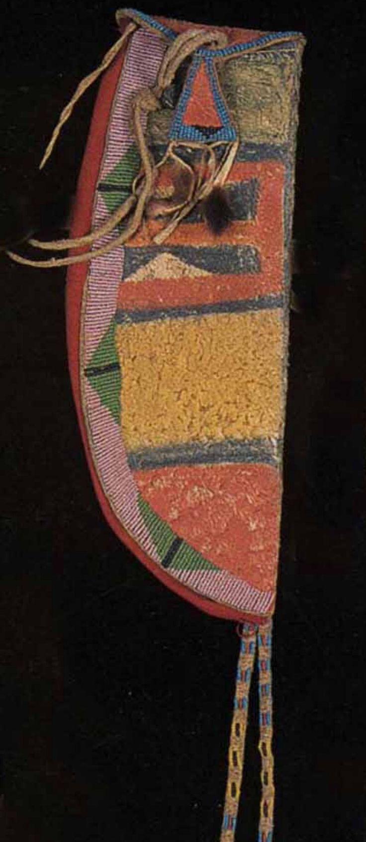 Ножны, Кроу. Деталь. Коллекция Fenn.  Период 1850-1875. Материалы: сыромятная кожа, краска, стеклянный бисер, красная шерсть, кожа, шкура выдры, красная и синяя охра. Общая длина 16,5 дюймов. Splendid Heritage.