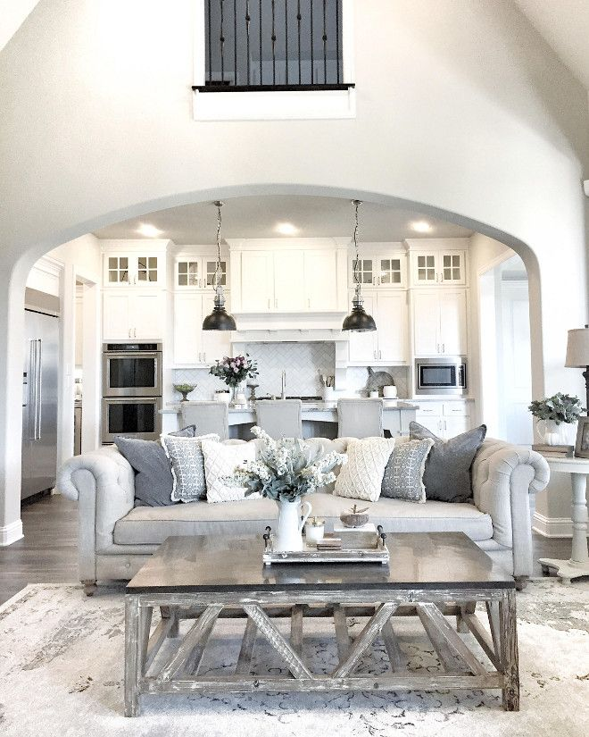 why this living room area has the huge arch in the middle of the room making it look calm and the sealing bigger - Home Room Decor