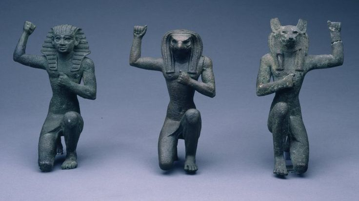 Bronze figure of a jackal-headed deity, hollow-cast, perhaps Duamutef, kneeling and wearing kilt and head-cloth, originally inlaid with lapis lazuli, small fragment of which survives, ears and back of head damaged, one fist clenched at breast and the other raised aloft, the latter has been repaired, the exterior has been chased in order to provide a ground for gilding, tiny sections of which survive.