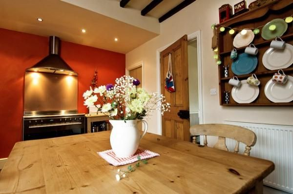 Stone flooring is carried through to the back of the cottage where a wood burning stove provides comfort and warmth to a charming farmhouse style kitchen