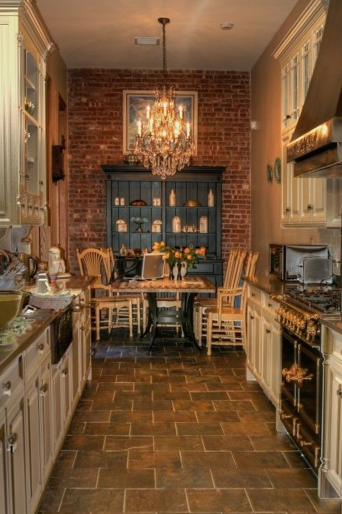 brick and crystal chandelier: a match made in heaven..my kind of kitchen love the rustic tile floors and brick wall.   Want it!  :))