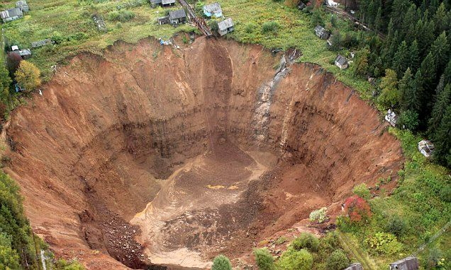 Holiday homes teeter precariously over 250ft deep sinkhole in Russia
