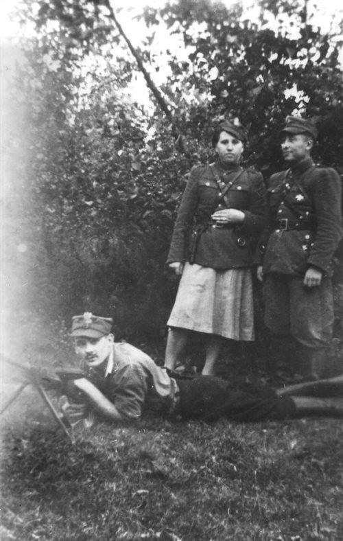 """Od prawej: szef PAS powiatu NZW Bielsk Podlaski por. Kazimierz Krasowski """"Głuszec"""" i Janina Jankowska """"Baśka"""". Leży: Arkadiusz Michalak """"Orlik"""" (zginął 8 września 1953 w walce z UB). Oddziały PAS Powiatu NZW Bielsk Podlaski walczyły w latach 1945–1954. W 1947 (już po amnestii) powstawały nowe, np. NN """"Mokrego"""" i NN """"Jesiona""""."""