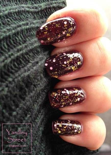 Really interesting glitter top coat with yellow gold flakes, pale pink hexagons and tiny dots, reddish strands and black dots. Worn over a plum base. #nails #manicure