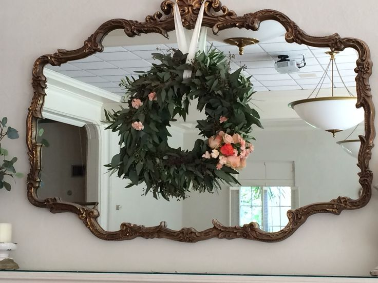 hanging above the mantles, loose and lovely eucalyptus and olive leaf wreaths are adorned with peach and orange roses, stock and mini carnations.