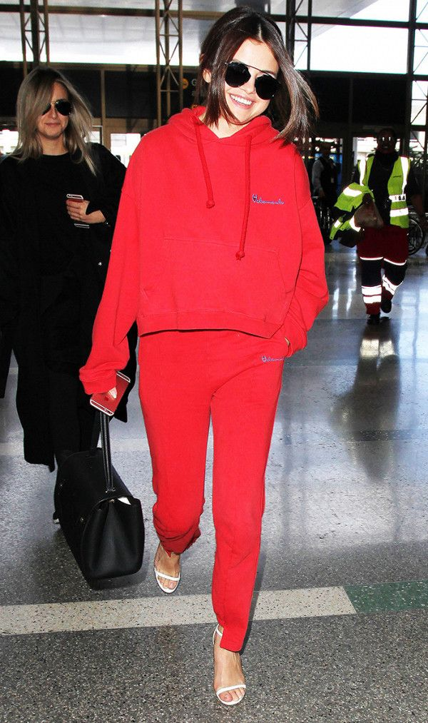 Selena Gomez in bright red hoodie and sweatpants at the airport.