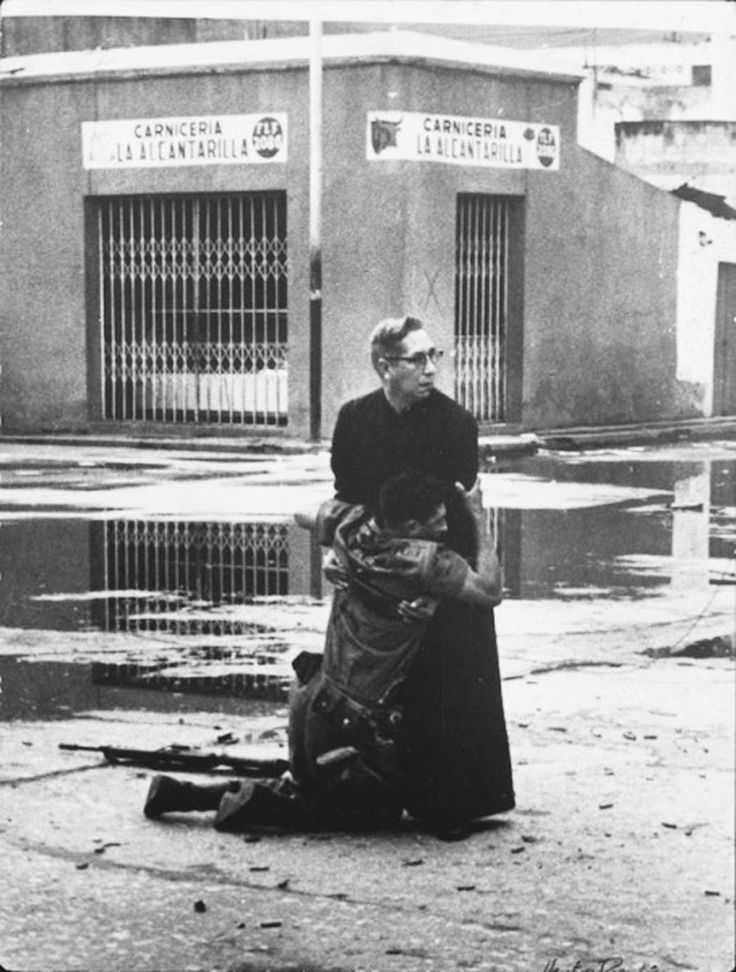 """A Venezuelan soldier clings to the soutane of Priest Luis Padillo, who is offering last rites to the dying amid an active warzone. """"Carniceria"""" in the background meaning """"Butcher's Shop"""" also translates to """"Slaughter, Carnage"""". 1962."""