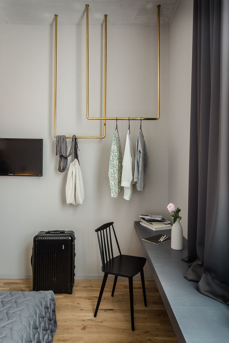 Bold Hotel in Germany   Custom brass clothes hangers, instead of a full closet, take up the empty space above the built-in shelf.