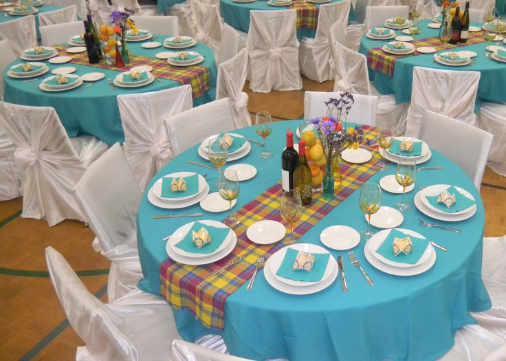 Tables with teal tablecloths, theme plaid table runner, centerpiece vase with lemons and oranges, glass bottles with wild flowers, origami menu and wine (seating arrangement indicator)