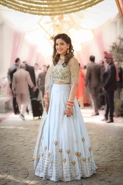 Light Lehengas - Sky Blue Lehenga with Gold Embroidery | WedMeGood | Sheer Embroidered Gold Blouse with High Waisted Lehenga and Gold Flowers #wedmegood #indianbride #indianwedding #lightlehengas #sisterofthebrideoutfit #sisterofthebride #lehenga #aqua