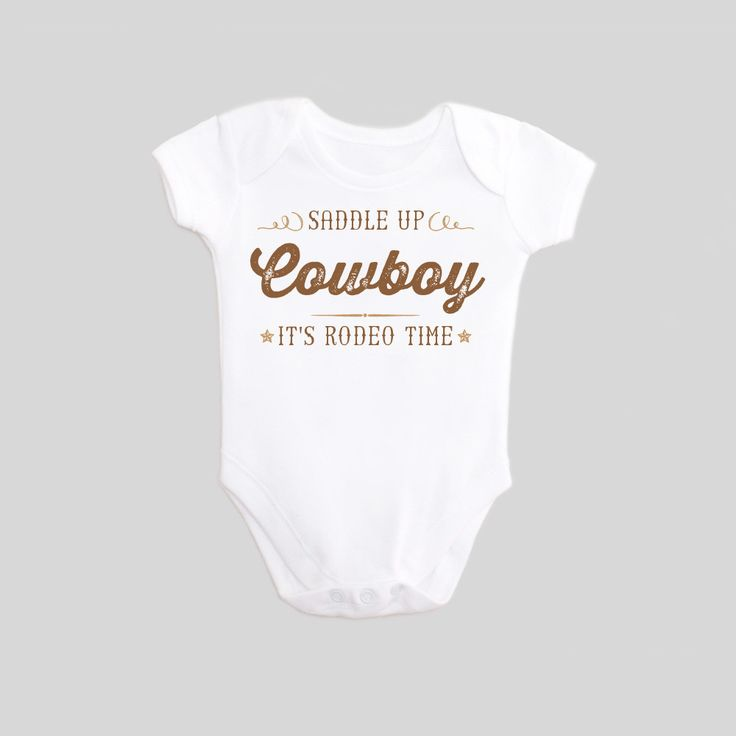 This Cowboy shirt is printed with Saddle Up - It's Rodeo Time! in brown lettering on a white baby bodysuit one-piece outfit. This Western Rodeo Outfit is the perfect cowboy apparel for your little Cow