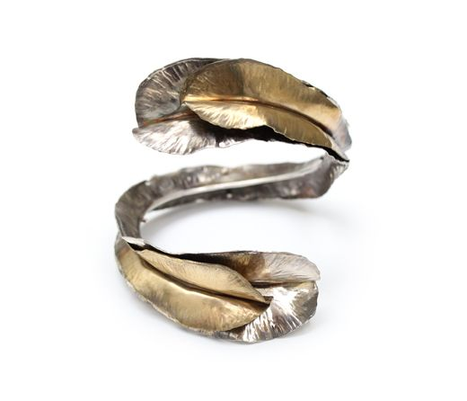 Sterling silver, brass.  Fits wrists up to 2.5 inches wide