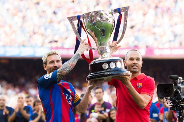 Lionel Messi (L) and Andres Iniesta (R) of FC Barcelona lift up the Spanish La Liga 2015-2016 season trophy before the La Liga match between FC Barcelona and Real Betis Balompie at Camp Nou on August 20, 2016 in Barcelona, Spain.