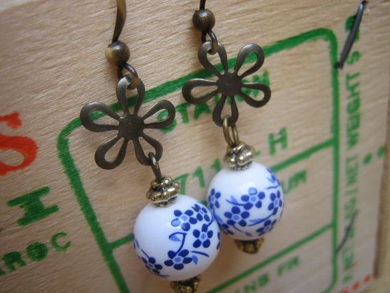 Antiqued brass flower charms and small brass beads echo the floral theme of these Chinese porcelain beads. Nickel free brass fish hook ear wires make these lightweight earrings easy to wear, and they come with small stoppers to keep them firmly in place.  $22.00
