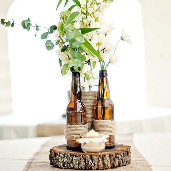 Este lindo modelo de centro de mesa foi usado num casamento realizado no quintal da casa dos pais da noiva, apenas com os familiares e os amigos mais próximos, num clima mais íntimo e com uma decoração artesanal e rústica. 🏡💞 A criatividade ficou por conta do mix de materiais usados para compor este arranjo: a juta combinou muito bem com o suporte feito de tronco de árvore; a vela trouxe um pouco de charme e romantismo a este estilo rústico de decoração e, como vasos de flores, foram…
