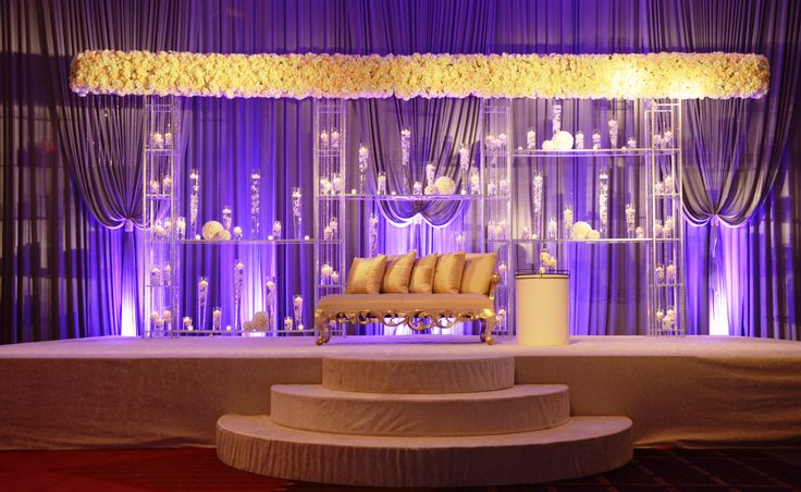 Modern Indian wedding ceremony with wide all floral mandap design with pilsner glasses filled with roses and candles.