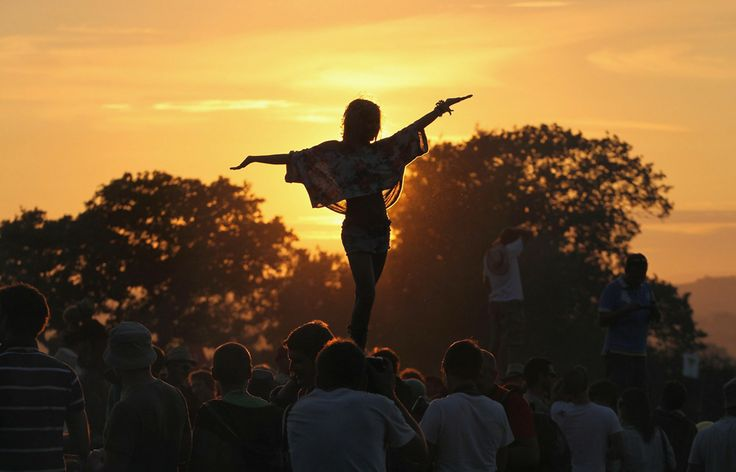 A girl standing during before the sunset at the Glastonbury Festival 2010