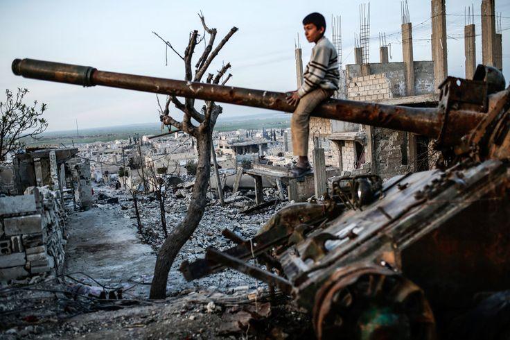 Un bambino seduto su un carro armato a Kobane, il 27 marzo 2015. - Yasin Akgul, Afp