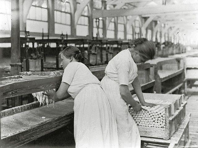 Vrouwen pakken de kaarsen van de band en knippen de lonten op maat…