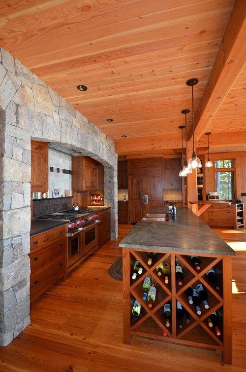 Dieses rustikale offenes Konzept Küche verfügt über eine längliche Kücheninsel, die gegenüber den kochenden Bereich eingerahmt in majestätischen steinernen Mauer steht. Foto von Bonin Architekten & Associates