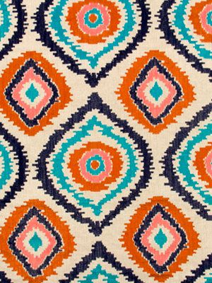 A modern ikat upholstery fabric in an embroidered design of tangerine, navy blue and turquoise on a natural woven linen background. This fabric